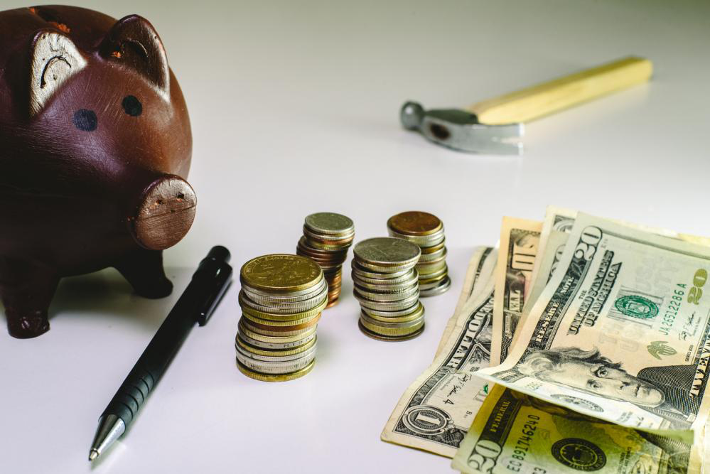 Money and coins next to a piggybank and hammer depicting cost-saving services