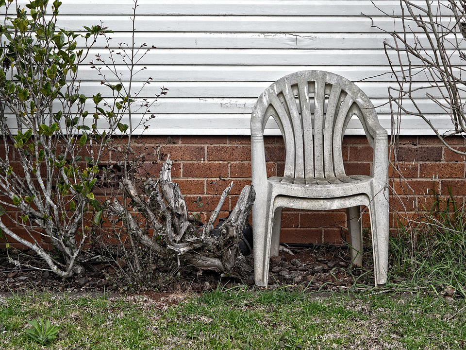 A couple of old and dirty chairs in the backyard that can be recycled