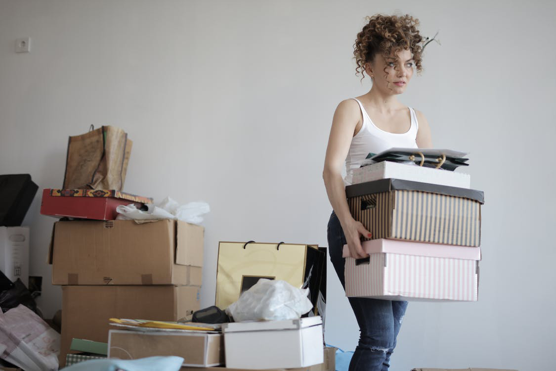 A woman lifting boxes to sort out and organize.A woman lifting boxes to sort out and organize.