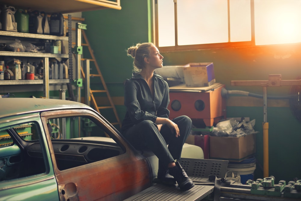 Woman sitting on a car looking around things stored in the garage