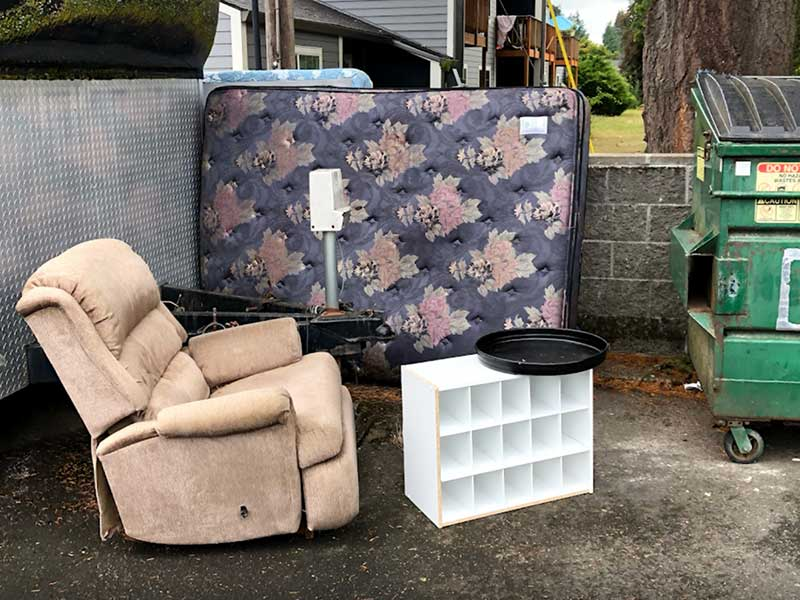 Old and abandoned sofa, mattress, and other furniture tossed on the road